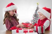 Composite image of cute siblings with gifts — Stock Photo