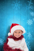 Composite image of cute little girl wearing santa hat and tinsel — Foto Stock