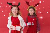 Festive little girls holding gifts — Stock Photo