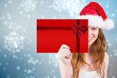 Festive redhead holding gift — Stock Photo