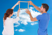 Composite image of couple deciding to hang picture — Stock Photo