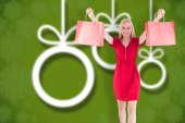Composite image of pretty blonde in red dress holding shopping b — Stock Photo