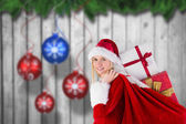 Festive blonde carrying sack of presents — Foto de Stock