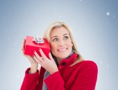 Festive blonde holding red gift  — Stock Photo