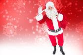 Santa holding a sack and waving — Stock Photo