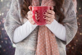 Composite image of woman in winter clothes holding a hot drink — Stock Photo