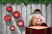 Festive blonde looking into glowing gift — Stockfoto