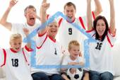 Family celebrating a goal at home — Stock Photo