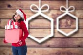 Composite image of happy brunette in santa hat holding many gift — Stock Photo