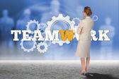 Thinking businesswoman against teamwork text — Stock Photo