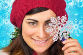 Brunette in hat holding snowflake — Stock Photo