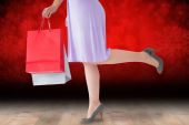 Composite image of mid section of woman in dress holding shoppin — Stock Photo