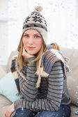 Cute blonde in winter hat sitting on couch posing — Stock Photo