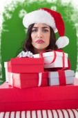 Composite image of confused brunette holding pile of gifts — Stock Photo