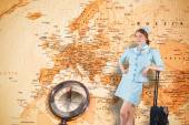 Pretty air hostess leaning on suitcase — Stock Photo