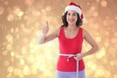 Composite image of festive fit brunette measuring her waist — Stock Photo