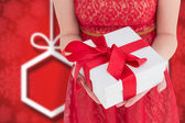 Pretty woman in red dress offering present — Stock Photo