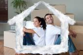 Bright couple with unpacking boxes — Stock Photo