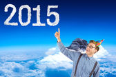 Hipster pointing at 2015 cloud shape — Stock Photo