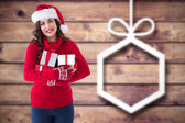 Composite image of festive brunette holding many gifts — Stock Photo
