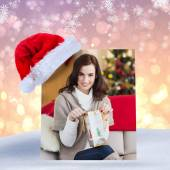 Brunette opening a gift on the couch at chris — Stockfoto
