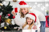 Festive mother and daughter decorating tree — Stock Photo