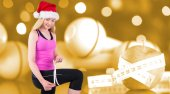 Composite image of fit festive young blonde measuring her thigh — Stock Photo