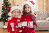 Festive siblings holding gifts — Stock Photo