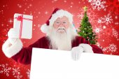 Santa shows present while holding sign — 图库照片