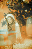 Composite image of festive little girl sitting in large gift — Zdjęcie stockowe