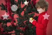 Festive little boy hanging bauble — Stockfoto