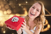 Composite image of portrait of a happy woman receiving a present — Stock Photo