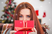 Festive redhead with gift on couch — Stockfoto