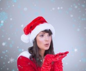 Pretty brunette in santa outfit blowing over — Stock Photo