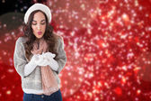 Composite image of pretty brunette in winter clothes blowing  — Stock Photo