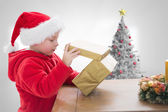 Composite image of cute boy opening gift — Stock Photo