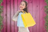 Composite image of woman with bags over shoulder — Stock Photo