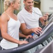 Male trainer timing his client on treadmill at gym — Stock Photo #62652809
