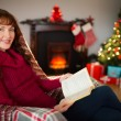 Cheerful redhead reading on the armchair at christmas — Stock Photo #62652831