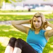 Fit blonde doing sit ups in the park — Stock Photo #62653637