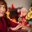 Smiling redhead holding red bauble at christmas — Stock Photo #62653709