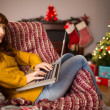 Redhead woman sitting on couch using laptop at christmas — Stock Photo #62654375