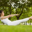 Woman doing boat pose in park — Stock Photo #62654687
