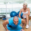 Female trainer assisting man with push ups at gym — Stock Photo #62655491