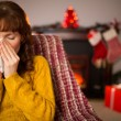 Woman sitting on sofa and blowing her nose at christmas — Stock Photo #62655791