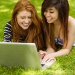 Relaxed women using laptop in park — Stock Photo #62655869
