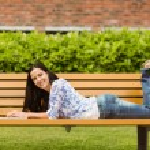 Peaceful brunette lying on bench using laptop — Stock Photo #62655899