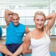Couple stretching hands behind back in yoga class — Stock Photo #62656757
