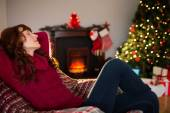 Pretty redhead resting on the armchair at christmas — Stockfoto