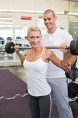 Male trainer helping woman with lifting barbell in gym — Stock Photo